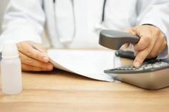 El doctor está llamando al paciente después de que lea diagnostique fotografía de archivo libre de regalías