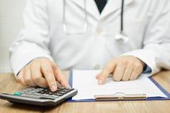 El doctor está utilizando la calculadora para sumar todos los costos imagen de archivo libre de regalías