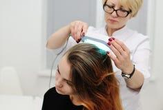 El doctor examina el cuero cabelludo un dispositivo especial con una lámpara ULTRAVIOLETA foto de archivo