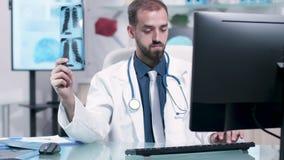 El doctor examina cuidadosamente un rayo X con los pulmones almacen de metraje de vídeo