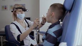 El doctor examina la garganta del niño pequeño con el telescopio ENT almacen de video