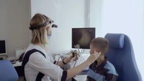 El doctor examina el oído del niño pequeño con el telescopio ENT metrajes