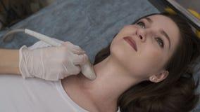 El doctor examina su cuello paciente del ` s con un dispositivo del ultrasonido almacen de video