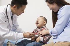 El doctor Examining Baby Boy en oficina Imagen de archivo