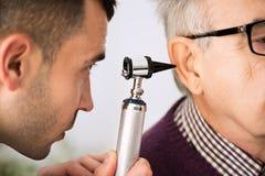 El doctor Examining Ear de un paciente fotografía de archivo libre de regalías