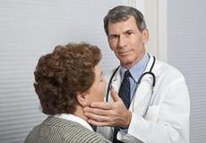 El doctor Examining Female Patient para los síntomas de la gripe Imagenes de archivo