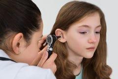 El doctor Examining Patient Ear con el otoscopio Foto de archivo libre de regalías