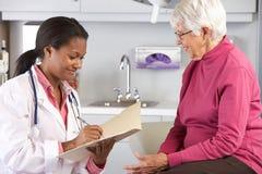 El doctor Examining Senior Female Patient fotografía de archivo