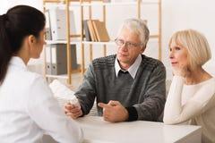 El doctor Explaining Prescription Medication a los pares mayores fotos de archivo