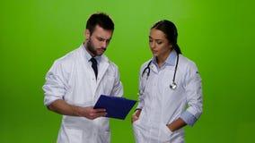 El doctor explica a la enfermera qué tratamiento la necesidad paciente almacen de metraje de vídeo