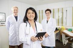 El doctor feliz Holding Tablet Computer mientras que se coloca con Colleag fotografía de archivo