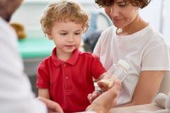 El doctor Giving Vitamins a Little Boy Fotografía de archivo libre de regalías