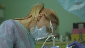 El doctor hace la operación en una máscara protectora, herramientas profesionales 4K 3840x2160 metrajes