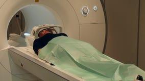 El doctor hace la tomografía del cerebro para una mujer en la exploración de MRI almacen de metraje de vídeo