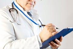 El doctor hace una entrada en la tarjeta paciente imagenes de archivo
