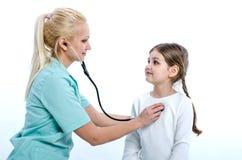 El doctor hace una inyección en los labios de un paciente El pediatra escucha la muchacha con la ayuda de un phonendoscope Imágenes de archivo libres de regalías