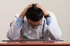 El doctor Having Stress In la oficina Imágenes de archivo libres de regalías