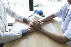 El doctor hizo un acuerdo con los pacientes con la tensión arterial alta de mantener salud foto de archivo libre de regalías