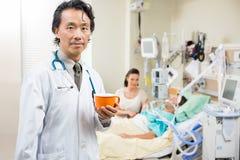 El doctor Holding Coffee Cup con el paciente que descansa adentro Fotografía de archivo libre de regalías