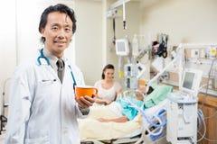 El doctor Holding Coffee Cup con el paciente que descansa encendido Imágenes de archivo libres de regalías