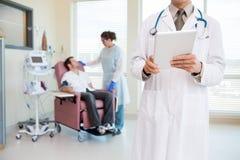 El doctor Holding Digital Tablet en Chemo Room Fotografía de archivo