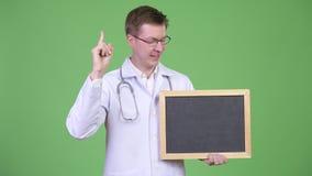 El doctor Holding Empty Blackboard del hombre con Copyspace metrajes