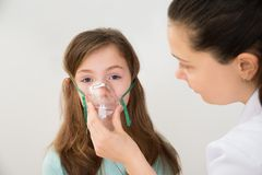 El doctor Holding Inhaler Mask para la muchacha que respira Foto de archivo libre de regalías