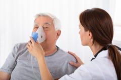El doctor Holding Oxygen Mask sobre la cara del hombre fotos de archivo libres de regalías