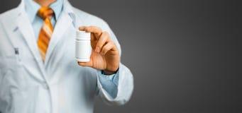 El doctor Holding una botella de píldoras entre sus fingeres en Grey Background Atención sanitaria, medicina, concepto del seguro fotos de archivo