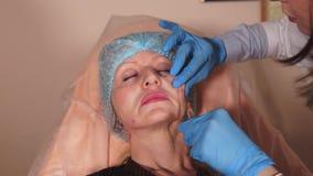 El doctor inyecta debajo de la piel paciente del ` s una droga con el ácido hialurónico metrajes
