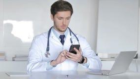 El doctor joven Browsing Smartphone en clínica metrajes