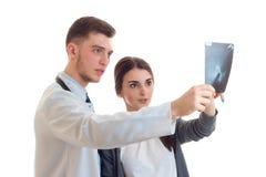 El doctor joven encantador estiró adelante una mano y muestra el primer de la radiografía de la muchacha Imagenes de archivo