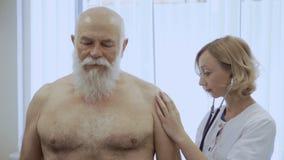 El doctor joven escucha los pulmones con el estetoscopio del hombre mayor almacen de video
