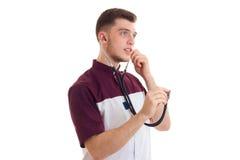 El doctor joven examina el estetoscopio en sus oídos fotos de archivo libres de regalías