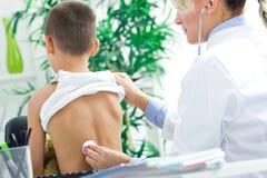 El doctor joven examina la parte posterior del muchacho con el estetoscopio fotos de archivo