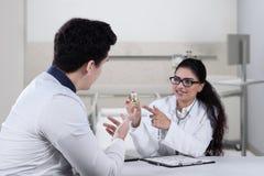 El doctor joven explica píldoras en su paciente Imágenes de archivo libres de regalías