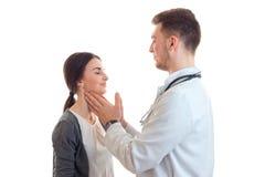 El doctor joven mueve suavemente a la muchacha linda de la garganta frágil aislada en un fondo blanco Foto de archivo libre de regalías