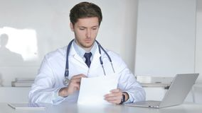 El doctor joven Reading Medical Report, haciendo papeleo almacen de metraje de vídeo