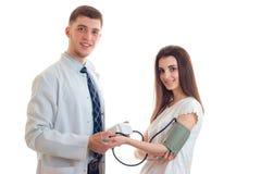 El doctor joven sonriente parece delantero y toma la presión de su paciente Fotografía de archivo