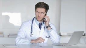 El doctor joven Talking con el paciente en el teléfono almacen de video