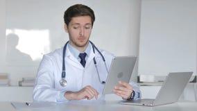 El doctor joven Talking con el paciente vía la charla video en la tableta metrajes