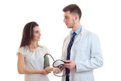 El doctor joven toma la presión de su primer sonriente paciente Imagen de archivo