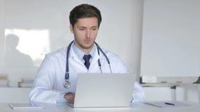 El doctor joven Working On Laptop en clínica almacen de metraje de vídeo