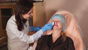 El doctor limpia la piel de la cara para una mujer que vino hacer procedimientos antienvejecedores almacen de video