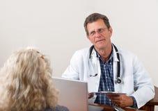 El doctor Listening al paciente femenino en oficina Imágenes de archivo libres de regalías