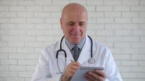 El doctor Listening un paciente escribe una prescripción y una sonrisa confiadas metrajes