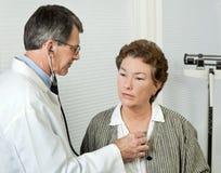 El doctor Listens el corazón del paciente Fotos de archivo