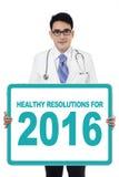 El doctor lleva a cabo al tablero con las resoluciones sanas para 2016 Fotos de archivo