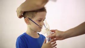 El doctor lleva un inhalador de la máscara en la cabeza del paciente almacen de video