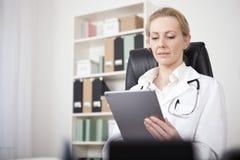 El doctor Looking de hembra adulta en su pantalla de la tableta Fotos de archivo